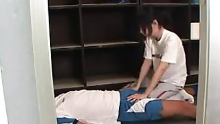 Asian masseuse gives her patient a nice massage sitting on