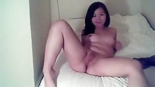 Asian girl takes off her clothes and masturbates with a toy on her bed
