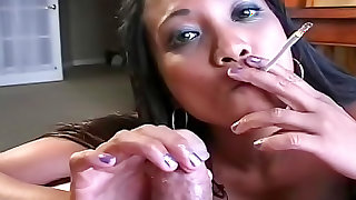 Asian bimbo with big tits is smoking on the bed