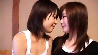 Two adorable Japanese girls in stockings passionately kiss